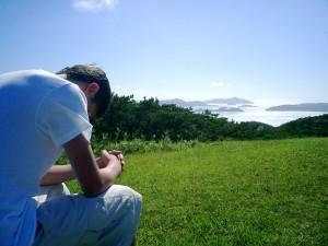 man-praying-field-alone-mountains